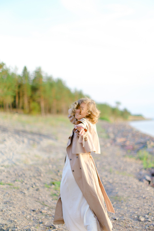 Young woman wearing coat and white dress standing on sea beach with trees in background. Concept of summer vacations photo session and freedom, happiness.