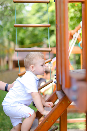 Little caucasian male baby playing on children playground. Concept of childhood and summer. Фото со стока