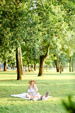 Young european blonde woman in hat sitting in park on plaid near fruits, grass and trees in background. Concept of summer picnic, resting on nature and healthy food.