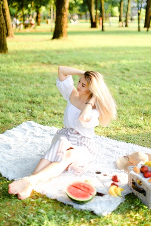 Young caucasian woman sitting on plaid with fruits in park. Concept of summer picnic, photo session in open air and vacations.