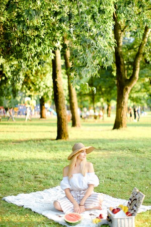 Young caucasian girl in hat sitting in park on plaid near fruits, grass and trees in background. Concept of summer picnic, resting on nature and healthy food.
