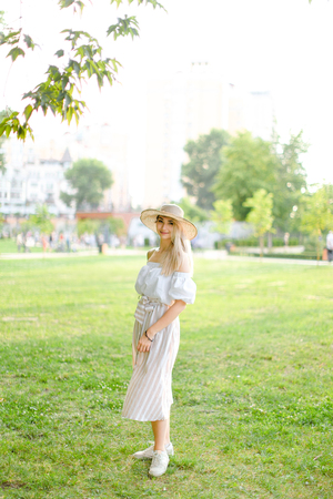 Young girl wearing hat and dress, standing in park on grass. Concept of summer season fashion and female person. Фото со стока