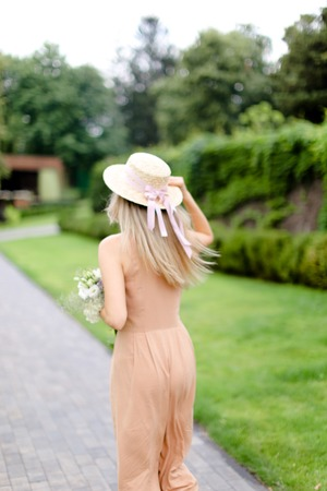 Back view of young blonde woman in body color overalls and hat standing in yeard. Concept of fashion and summer season.