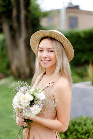 Young blonde girl standing in yeard with bouquet of flowers and wearing hat with overalls. Concept of yuoth and summer season, fashion.
