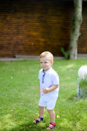 Little baby standing on grass. Concept of childhood and summer. Фото со стока