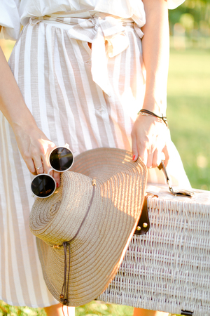 Close up bag, hat and sunglasses in female hands, dress in background. Concept of summer fashion.