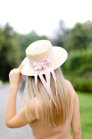 Back view of young blonde girl in body color overalls and hat standing in yeard. Concept of fashion and summer season.