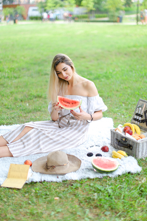 Girl sitting on plaid near fruits and hat, eating watermelon, grass in background. Concept of summer picnic and resting on weekends in open air.
