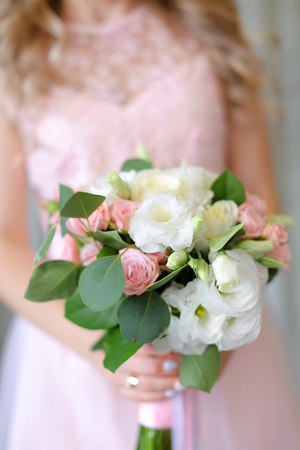 Close up cute bouquet of flowers in light pink dress background. Concept of wedding photo session and bride.