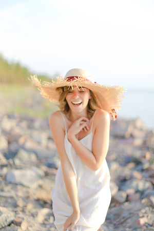 Young smiling woman in hat with red ribbon standing on shingle beach. Concept of summer vacations and resort.