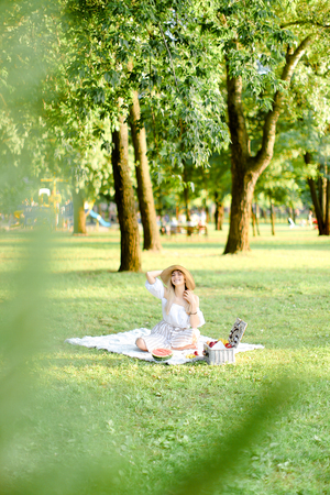 Young european blonde woman in hat resting on plaid with fruits in garden. Concept of summer picnic in park, nature and free time. Stock fotó