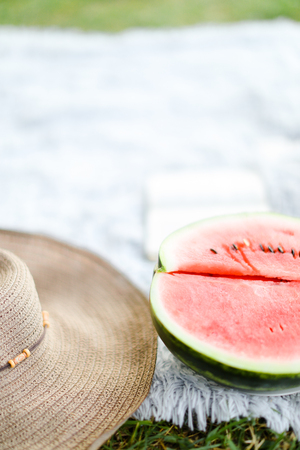 Juicy watermelon and hat on white plaid. Concept of summer season and picnic.