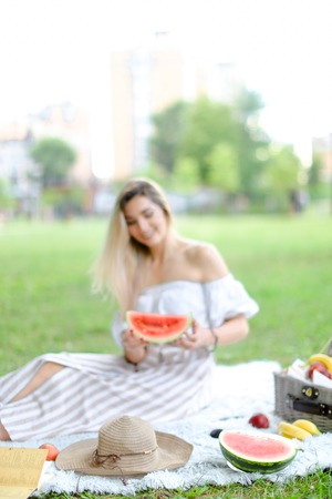 Young woman sitting on plaid near fruits and hat, eating watermelon, grass in background. Concept of summer picnic and resting on weekends in open air.