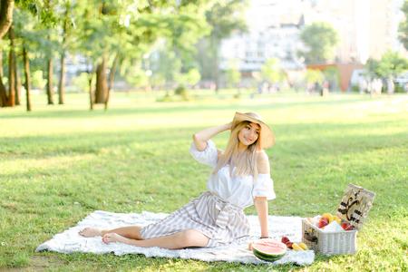 Junge blonde kaukasische Frau mit Hut, die im Park auf Plaid in der Nähe von Früchten sitzt, Gras im Hintergrund. Konzept des Sommerpicknicks, das auf Natur und gesundem Essen ruht.