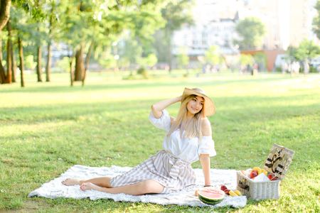 Young blonde caucasian woman in hat sitting in park on plaid near fruits, grass in background. Concept of summer picnic, resting on nature and healthy food.