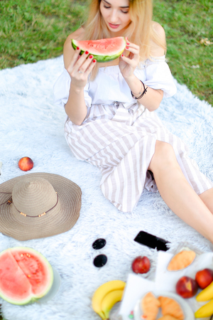 Caucasian blonde woman sitting on plaid near fruits and hat, eating watermelon, grass in background. Concept of summer picnic and resting on weekends in open air.