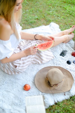 Young blonde girl sitting on plaid near fruits and hat, eating watermelon, grass in background. Concept of summer picnic and resting on weekends in open air.