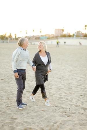 Pareja de jubilados caminando y tomados de la mano en la playa de arena. Concepto de personas mayores y relación.