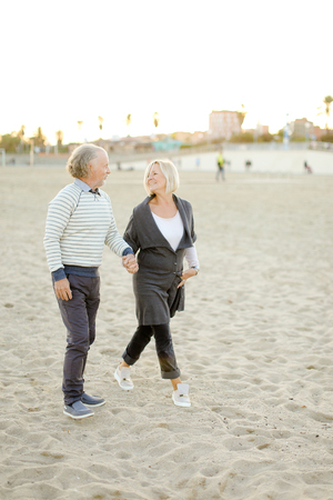 Pensioners couple walking and and holding hands on sand beach. Concept of elderly people and relationship.