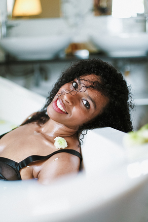 Young afro american woman relaxing in bath with flower on shoulder, wearing black swimsuit.. Concept of spa and personal care.