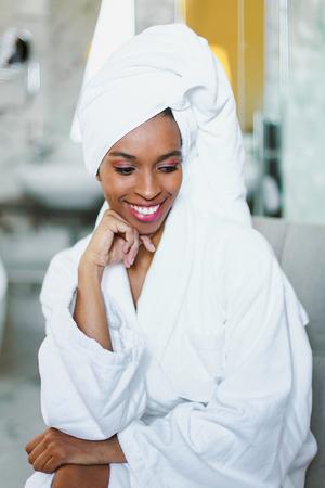 Junge süße afroamerikanische Frau, die im Badezimmer sitzt und weißen Bademantel trägt. Konzept der Entspannung und Körperpflege. Standard-Bild