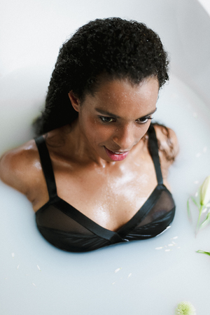 Portrait of black girl taking bath with foam, wearing swimsuit. Concept of spa, relax and personal care.