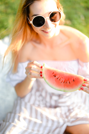 Young caucasian girl in sunglasses eating watermelon. Concept of healty food and summer season, vegeterian lifestyle. Фото со стока