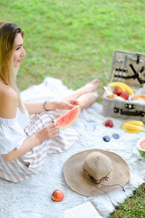 Young blonde female person sitting on plaid near fruits and hat, eating watermelon, grass in background. Concept of summer picnic and resting on weekends in open air.