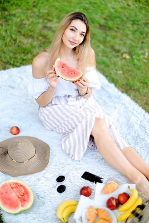 Young nice girl sitting on plaid near fruits and hat, eating watermelon, grass in background. Concept of summer picnic and resting on weekends in open air. Фото со стока