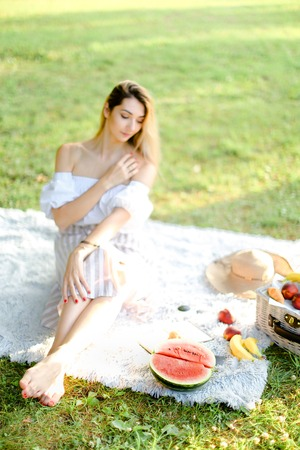 Young girl having picnic on plaid and sitting in park with fruits. Concept of resting in ope air, leisure time and summer season