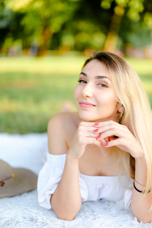 Young girl with red nails lying in park on plaid. Concept of having free time, picnic and summer vacations. Фото со стока