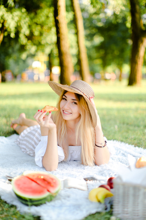 Young caucasian girl in hat with croissant lying in park on plaid near watermelon. Concept of having free time, picnic and bakery products.