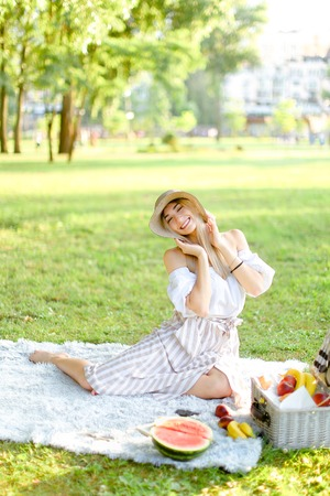 Young beautiful caucasian woman in hat sitting in park on plaid near fruits, grass in background. Concept of summer picnic, resting on nature and healthy food.