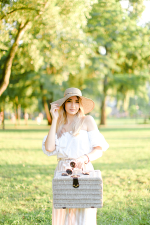 Young nice woman wearing hat and dress standing in garden with bag. Concept of beautiful female person, summer fashion and walking in park. Фото со стока