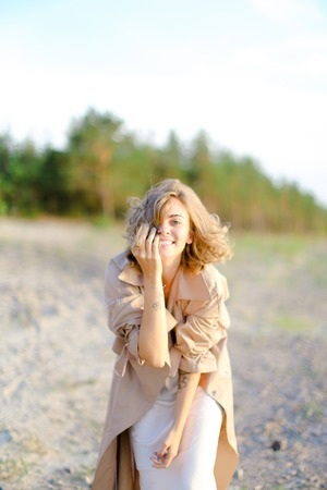 Smiling blonde woman wearing coat standing on sand with trees in background. Concept of happiness, youth and fashion.