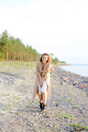 Blonde young woman standing on sea beach and wearing coat with white dress. Concept of happiness, youth and fashion, summer vacations.