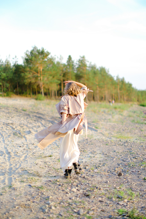 Young blonde woman turning around on sand and wearing coat with white dress. Concept of happiness, summer vacations and fashion.