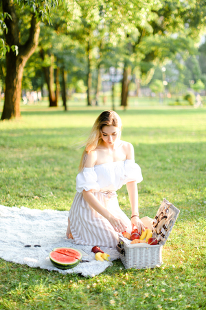 Young woman preparing for picnic in park, sitting on plaid near box and waterlemon. Concept of having leisure time, resting in open air and summer season.