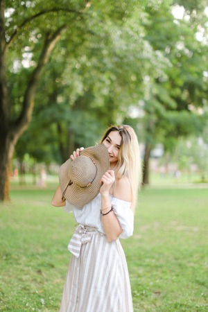 Young jocund girl wearing dress, standing in park and keeping hat. Concept of summer season and fashion.