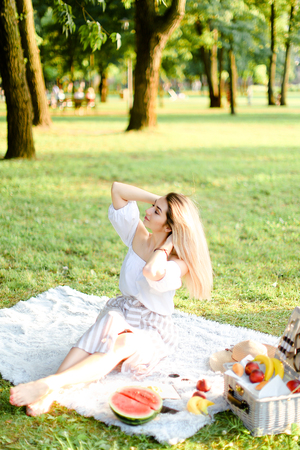 Young woman sitting on plaid with fruits in park. Concept of summer picnic, photo session in open air and vacations. Фото со стока