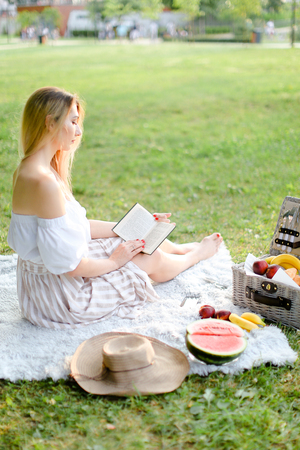 Young blonde girl reading book and sitting on plaid near fruits in park. Concept of having summer picnic and leisure time.