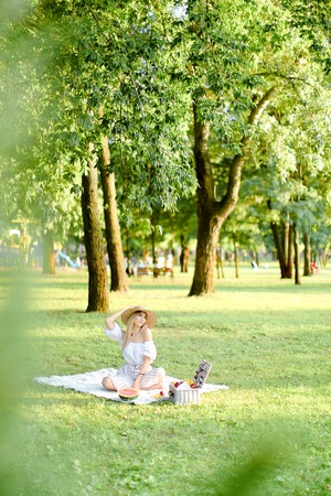 Young caucasian blonde woman in hat sitting on plaid with fruits in garden. Concept of summer picnic in park, nature and free time. Фото со стока