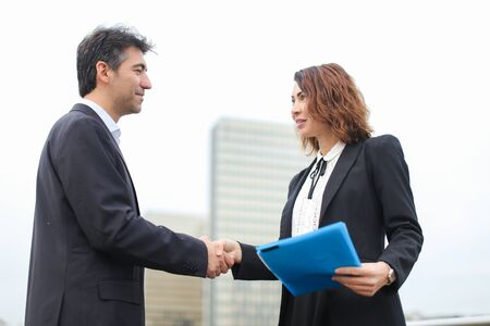 man with smartphone going towards woman with blue folder of documents, old IT business partners meet to discuss work. Middle-aged Americans in strict suits shaking hands smiling. Concept of innovative technologies, modern clothes or cooperation.