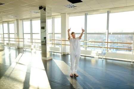 Blonde dancer spotting  at studio with window in background. Young male person wears white shirt and pant for training. Concept of basic dance elements. 免版税图像