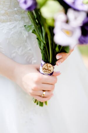 Closeup bridal hands keeping violet bouquet of flowers. Concept of wedding photo session and floristic art.
