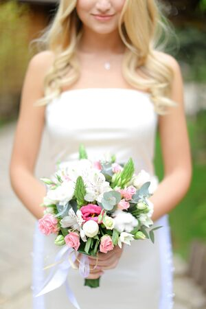 Young blonde bride keeping bouquet of flowers. Concept of wedding and floristic art. 版權商用圖片