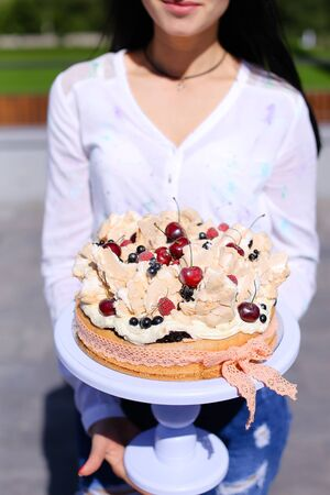 Woman wearing white blouse keeping birthday cake. Concept of sweets and tasty food for party.
