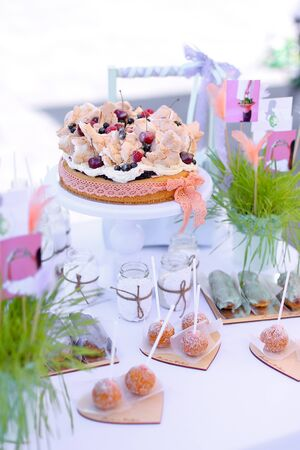 Sweet cakes on white table for birthday party. Concept of sweets and tasty food.