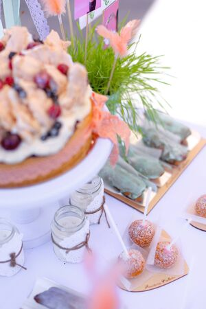 Sweet delicious cakes on white table for birthday party. Concept of sweets and tasty food.