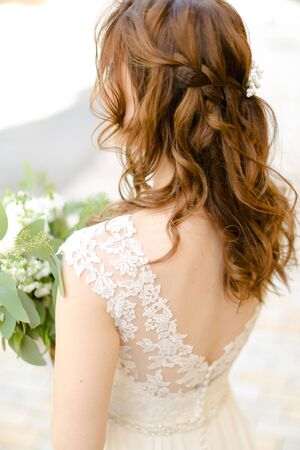 Back view of curls for bride keeping flowers. Concept of wedding photo session and stylish hair do.
